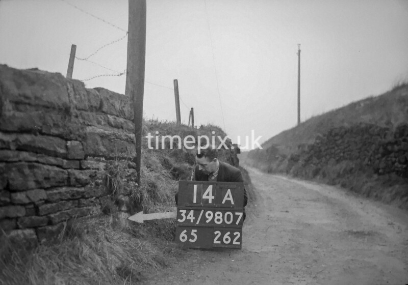 SD980714A, Man marking Ordnance Survey minor control revision point with an arrow in 1950s