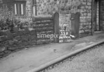 SD990635R1, Man marking Ordnance Survey minor control revision point with an arrow in 1950s