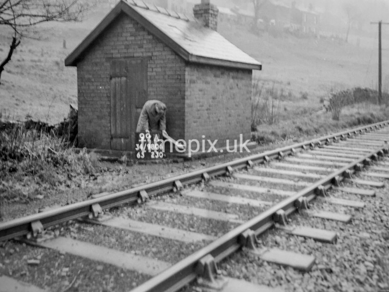 SD980699A, Man marking Ordnance Survey minor control revision point with an arrow in 1950s
