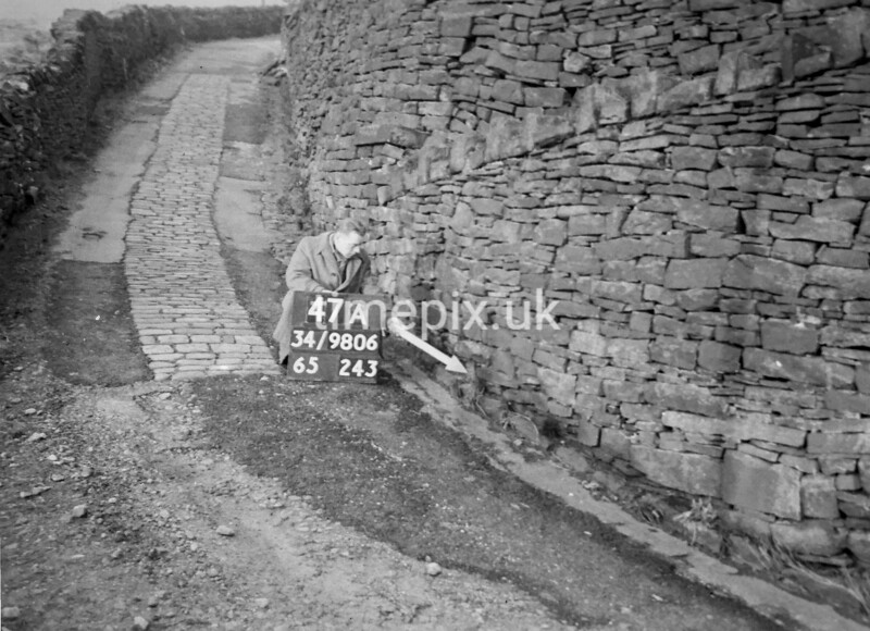SD980647A, Man marking Ordnance Survey minor control revision point with an arrow in 1950s