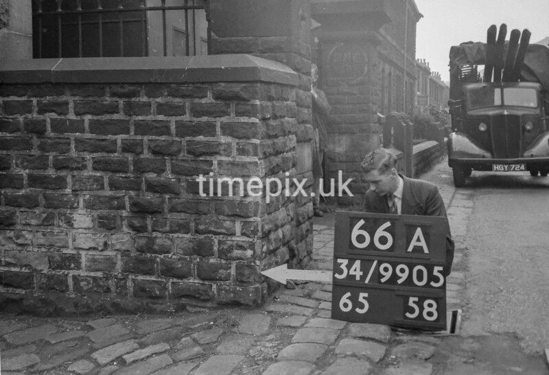 SD990566A, Man marking Ordnance Survey minor control revision point with an arrow in 1950s
