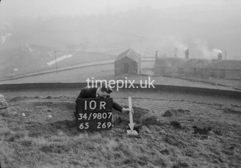 SD980710R, Man marking Ordnance Survey minor control revision point with an arrow in 1950s