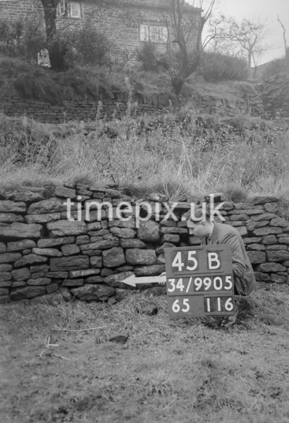 SD990545B, Man marking Ordnance Survey minor control revision point with an arrow in 1950s