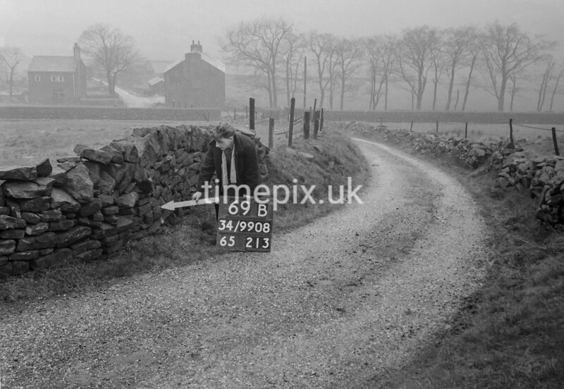 SD990869B, Man marking Ordnance Survey minor control revision point with an arrow in 1950s