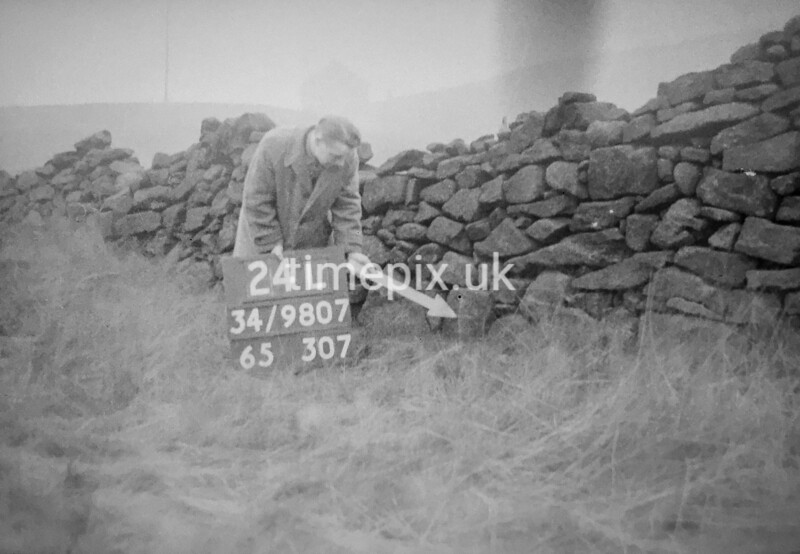 SD980724L, Man marking Ordnance Survey minor control revision point with an arrow in 1950s