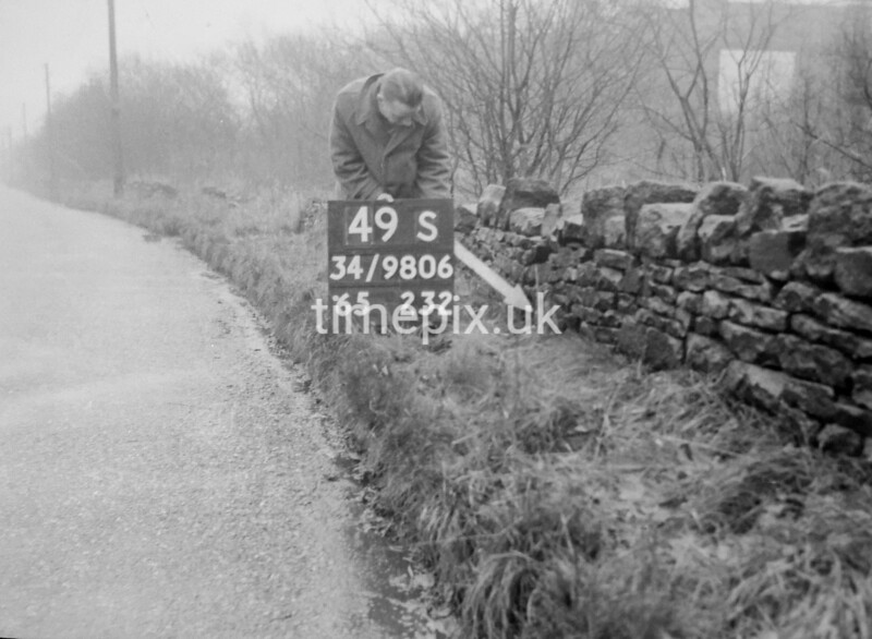 SD980649S, Man marking Ordnance Survey minor control revision point with an arrow in 1950s