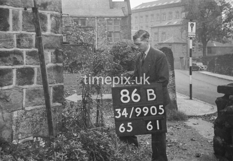 SD990586B, Man marking Ordnance Survey minor control revision point with an arrow in 1950s