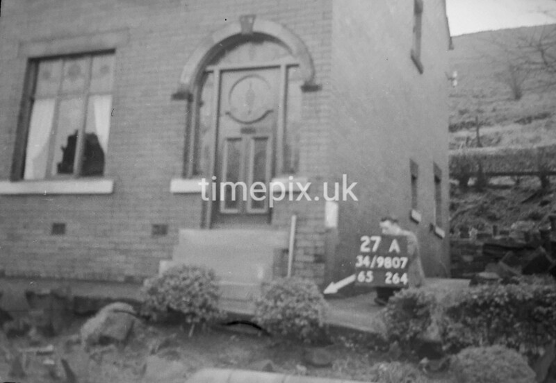 SD980727A, Man marking Ordnance Survey minor control revision point with an arrow in 1950s