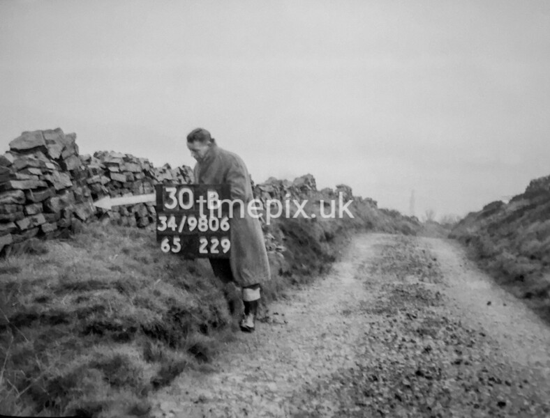 SD980630B, Man marking Ordnance Survey minor control revision point with an arrow in 1950s