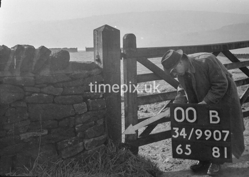 SD990700B, Man marking Ordnance Survey minor control revision point with an arrow in 1950s