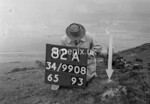 SD990882A, Man marking Ordnance Survey minor control revision point with an arrow in 1950s
