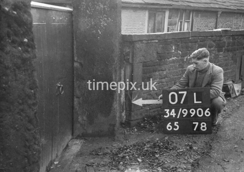 SD990607L, Man marking Ordnance Survey minor control revision point with an arrow in 1950s