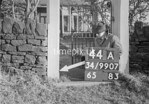 SD990744A, Man marking Ordnance Survey minor control revision point with an arrow in 1950s