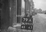 SD990579A, Man marking Ordnance Survey minor control revision point with an arrow in 1950s
