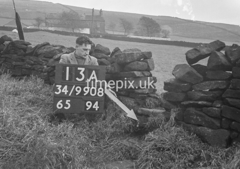 SD980813A, Man marking Ordnance Survey minor control revision point with an arrow in 1950s