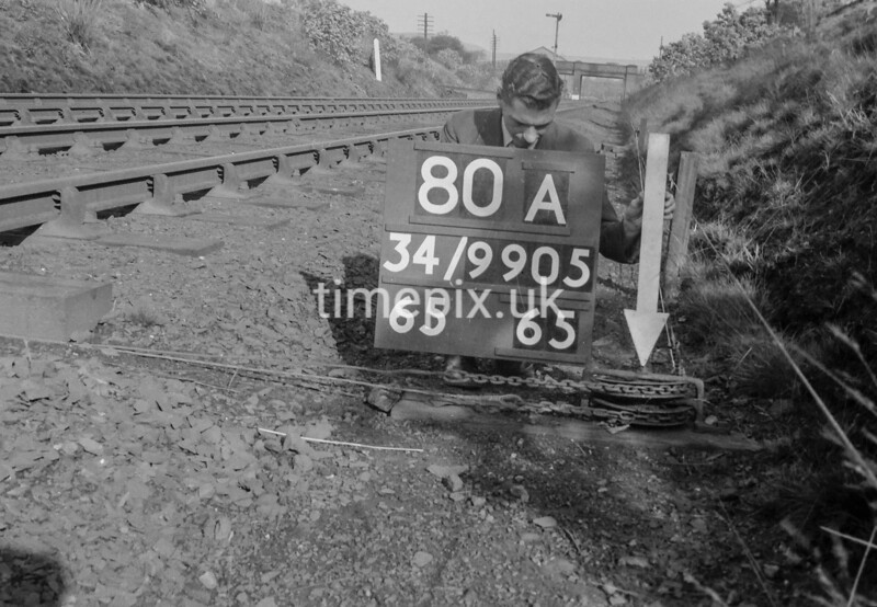 SD990580A, Man marking Ordnance Survey minor control revision point with an arrow in 1950s