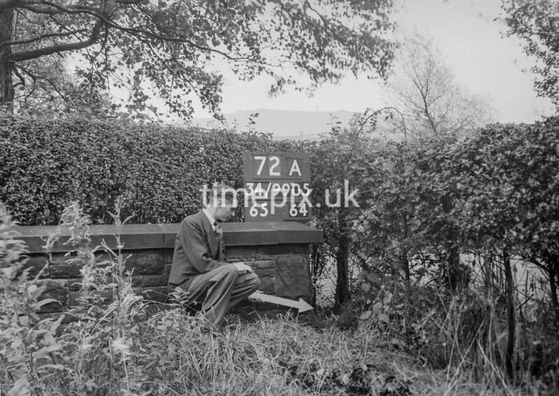 SD990572A, Man marking Ordnance Survey minor control revision point with an arrow in 1950s