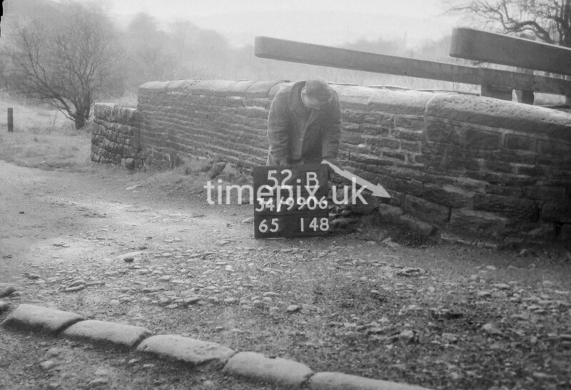 SD990652B2, Man marking Ordnance Survey minor control revision point with an arrow in 1950s