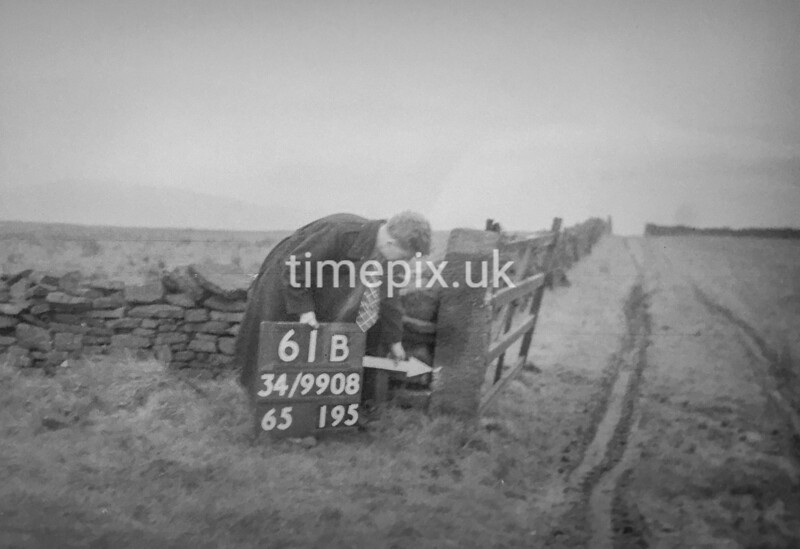 SD990861B, Man marking Ordnance Survey minor control revision point with an arrow in 1950s