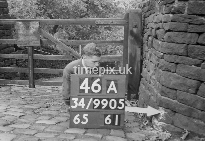 SD990546A, Man marking Ordnance Survey minor control revision point with an arrow in 1950s