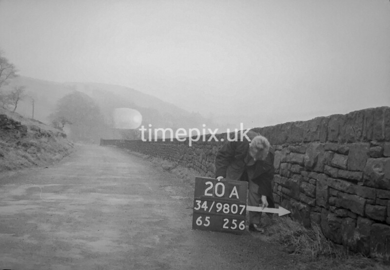 SD980720A, Man marking Ordnance Survey minor control revision point with an arrow in 1950s
