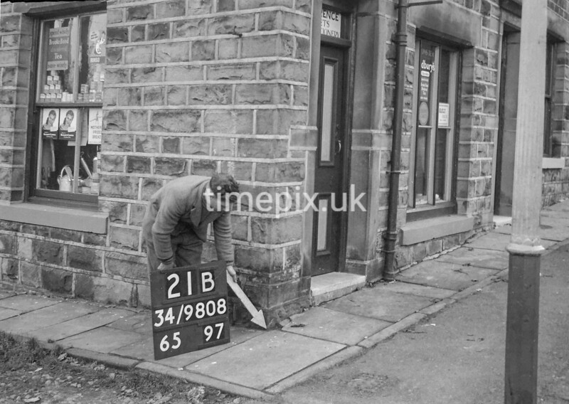 SD980821B, Man marking Ordnance Survey minor control revision point with an arrow in 1950s
