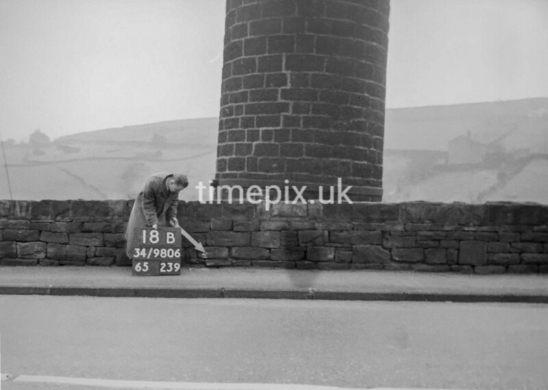 SD980618B, Man marking Ordnance Survey minor control revision point with an arrow in 1950s