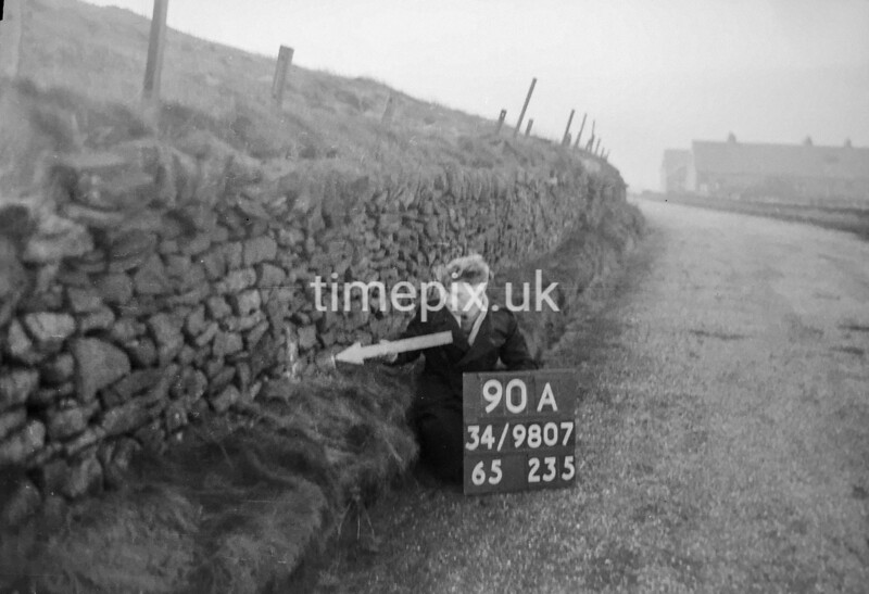 SD980790A, Man marking Ordnance Survey minor control revision point with an arrow in 1950s