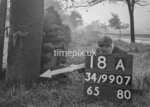 SD990718A, Man marking Ordnance Survey minor control revision point with an arrow in 1950s