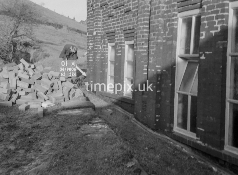SD980601A, Man marking Ordnance Survey minor control revision point with an arrow in 1950s