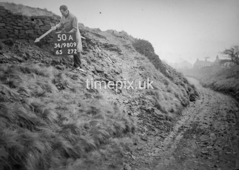 SD980950A, Man marking Ordnance Survey minor control revision point with an arrow in 1950s
