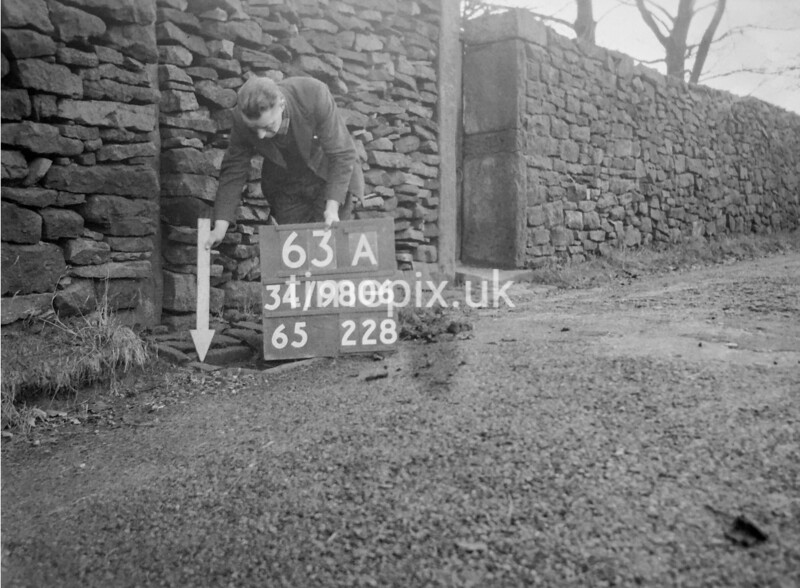 SD980663A, Man marking Ordnance Survey minor control revision point with an arrow in 1950s