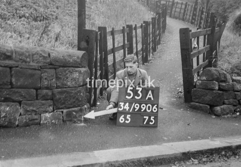 SD990653A, Man marking Ordnance Survey minor control revision point with an arrow in 1950s