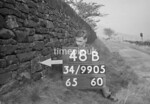 SD990548B, Man marking Ordnance Survey minor control revision point with an arrow in 1950s