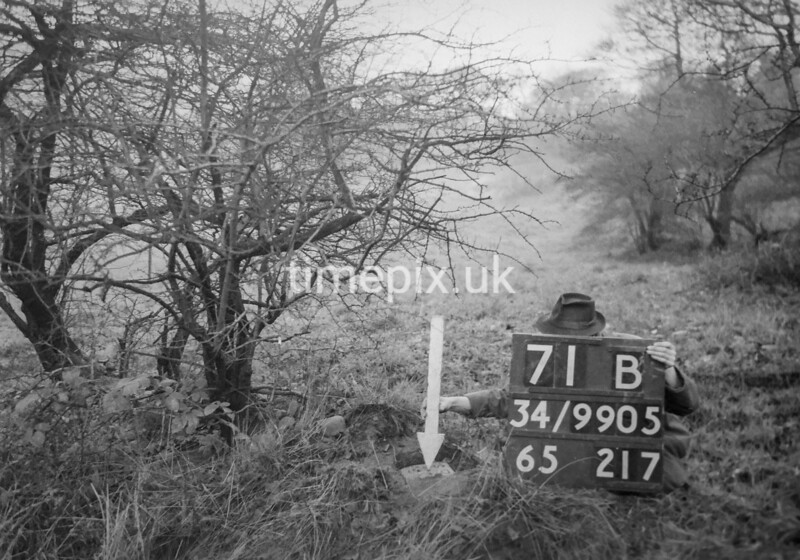 SD990571B, Man marking Ordnance Survey minor control revision point with an arrow in 1950s
