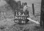 SD990719A, Man marking Ordnance Survey minor control revision point with an arrow in 1950s