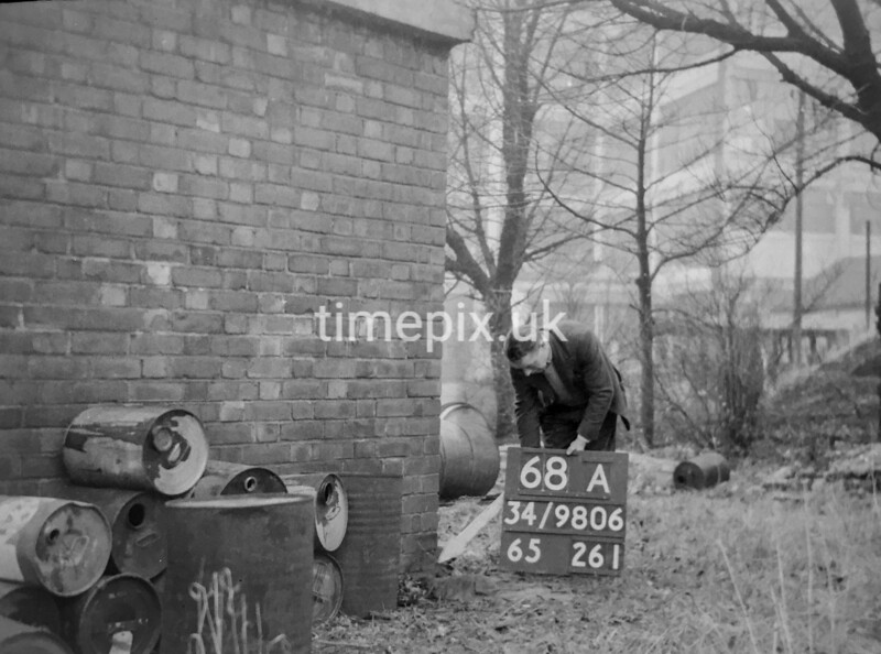 SD980668A, Man marking Ordnance Survey minor control revision point with an arrow in 1950s