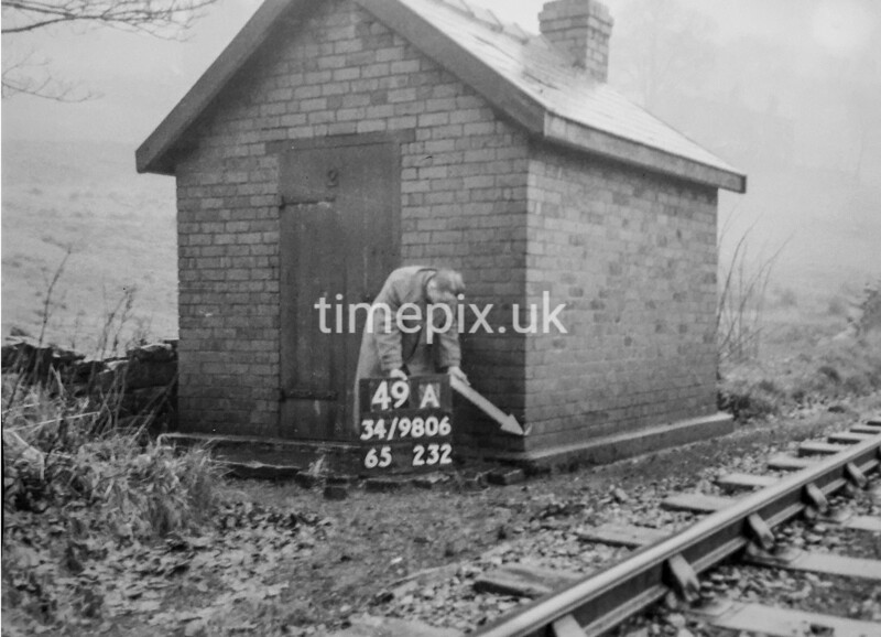 SD980649A, Man marking Ordnance Survey minor control revision point with an arrow in 1950s