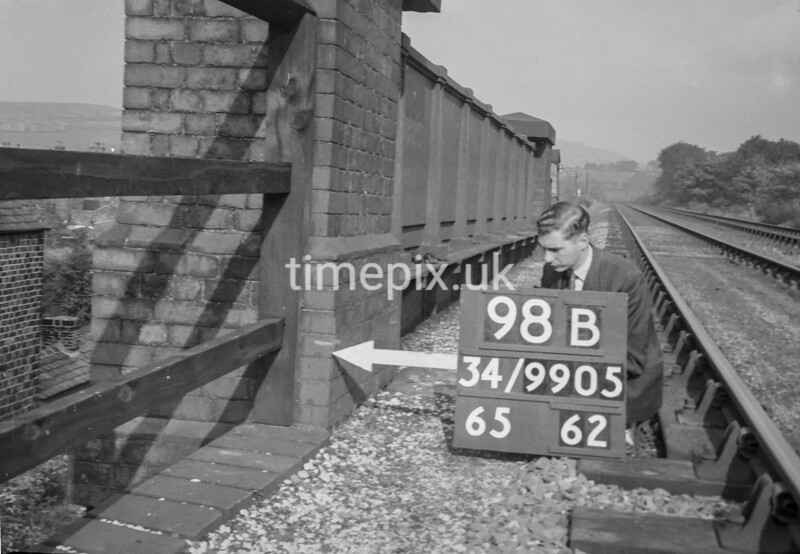 SD990598B, Man marking Ordnance Survey minor control revision point with an arrow in 1950s