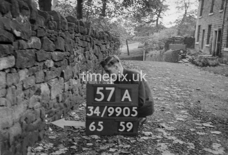 SD990557A, Man marking Ordnance Survey minor control revision point with an arrow in 1950s