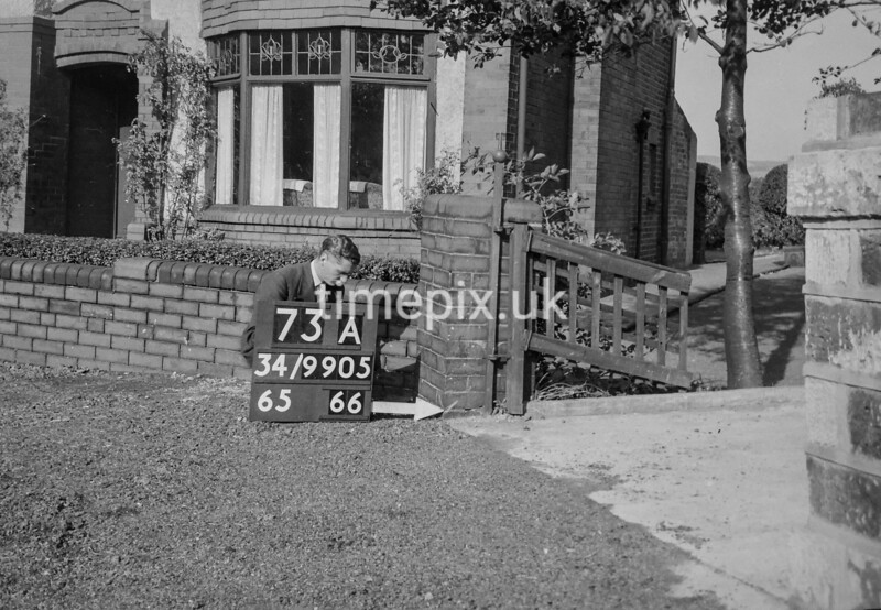 SD990573A, Man marking Ordnance Survey minor control revision point with an arrow in 1950s