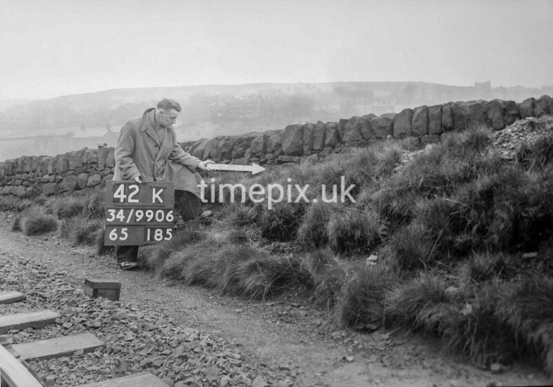 SD990642K2, Man marking Ordnance Survey minor control revision point with an arrow in 1950s