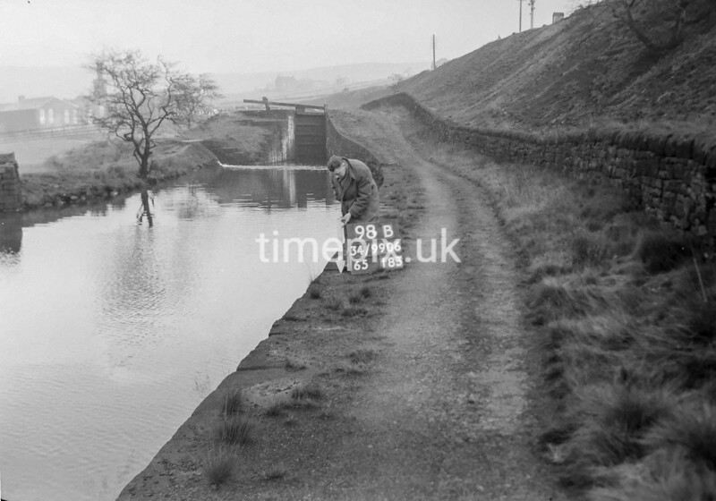 SD990698B, Man marking Ordnance Survey minor control revision point with an arrow in 1950s