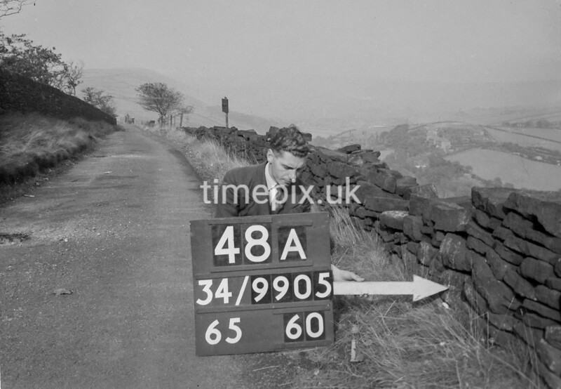 SD990548A, Man marking Ordnance Survey minor control revision point with an arrow in 1950s