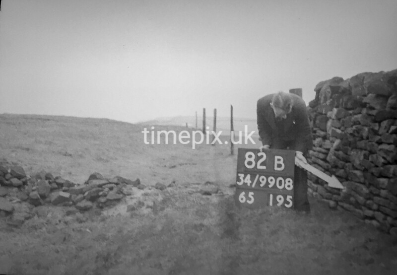 SD990882B, Man marking Ordnance Survey minor control revision point with an arrow in 1950s