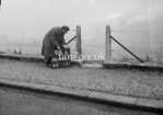 SD990798A, Man marking Ordnance Survey minor control revision point with an arrow in 1950s