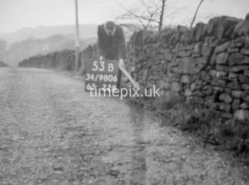 SD980653B, Man marking Ordnance Survey minor control revision point with an arrow in 1950s