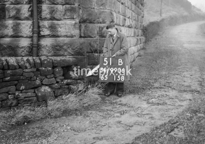 SD990651B2, Man marking Ordnance Survey minor control revision point with an arrow in 1950s
