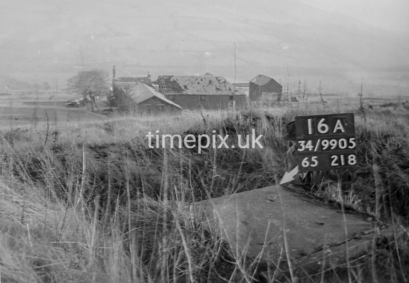 SD990516A, Man marking Ordnance Survey minor control revision point with an arrow in 1950s