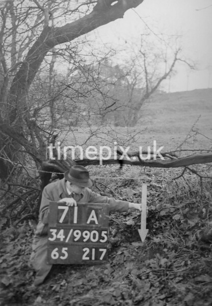 SD990571A, Man marking Ordnance Survey minor control revision point with an arrow in 1950s